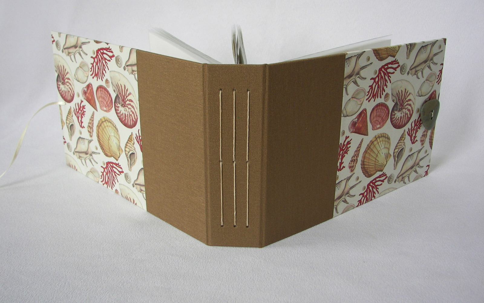 Kris is a master at combining materials like this sand-colored binding paired with a Rossi seashells paper.